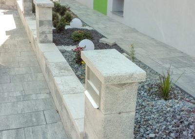Gartenmauer aus Betonsteinen mit Zaunsäulen und integriertem Briefkasten