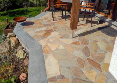 Terrasse aus Quarzit Polygonalplatten; mit Granit Dunkel eingefasst