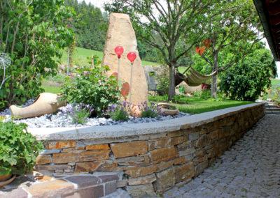 Natursteinmauer aus Gloria Gneis mit Abdeckplatte aus Neuhauser Granit
