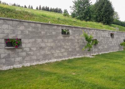 Stützmauer bestehend aus Beton-Mauersteinen in Felsen-Grau mit Abdeckplatte